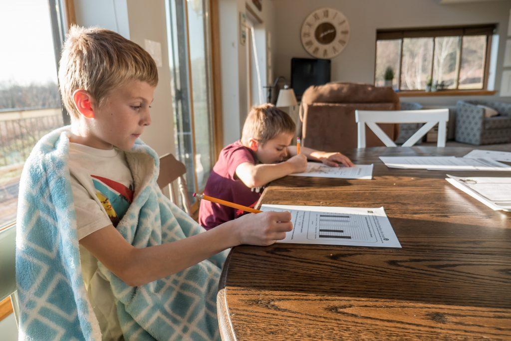 2 Jungen machen Hausaufgaben am Tisch