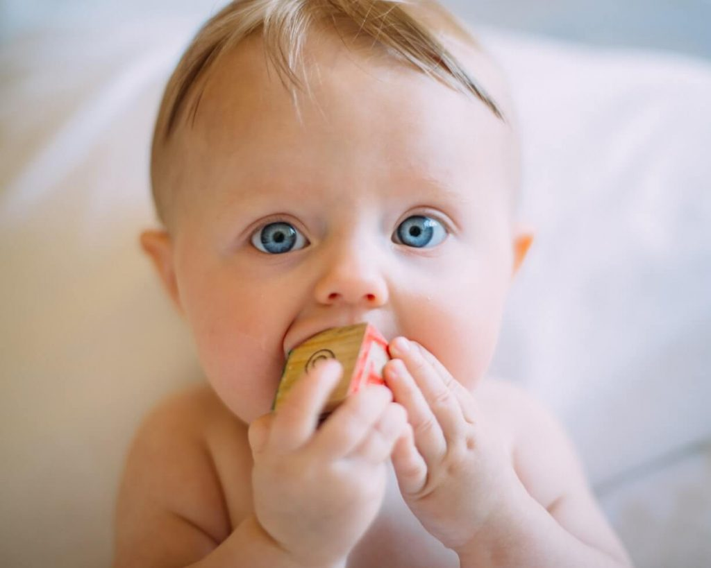 Baby mit blauen Augen spielt mit einem Spielzeug